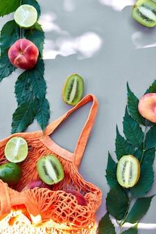 Postura plana da sacola de compras de malha ecológica com frutas pêssego, kiwi, limão na superfície cinza na luz solar, horário de verão. conceito de mercearia, cópia espaço, vista superior.