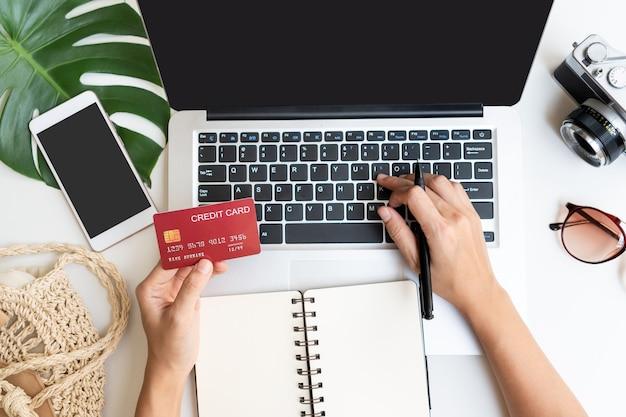 Postura plana das mãos de mulher digitando no laptop. verão, férias, planejamento de viagens conceito