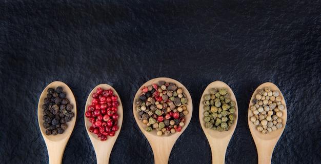 Postura plana de 5 tipos de pimenta em uma colher de pau em um fundo preto conceito de comida saudável
