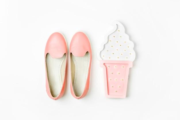 Postura plana de acessórios de moda feminina, sapatos e luzes de fada de sorvete em fundo de cor pastel. conceito de beleza e moda