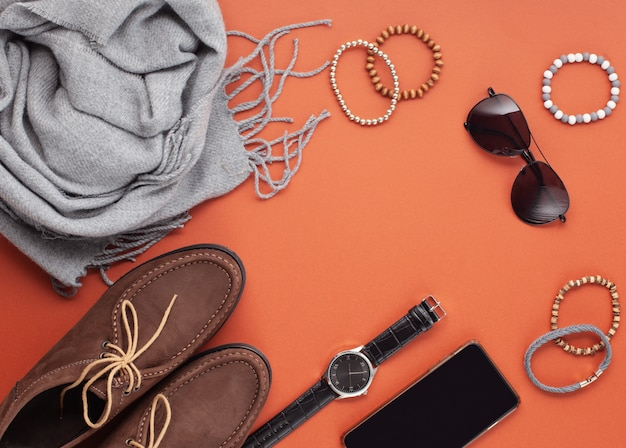 Postura plana de acessórios masculinos com sapatos, relógio, telefone, fones de ouvido, óculos de sol, cachecol sobre o fundo laranja