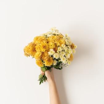Postura plana de amarelo e gengibre cair buquê de flores silvestres na mão das mulheres isolado no branco. camada plana, vista superior