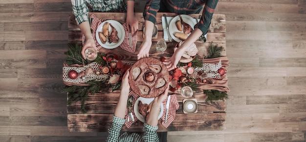 Postura plana de amigos mãos comendo e bebendo juntos. vista superior das pessoas, festa, reunião, comemorando juntos na mesa rústica de madeira