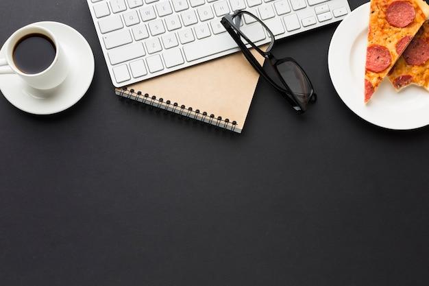 Postura plana de área de trabalho com notebook e pizza