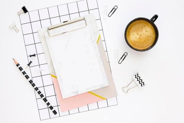 Postura plana de artigos de papelaria de escritório com bloco de notas e café