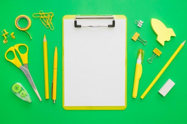 Postura plana de artigos de papelaria de escritório com bloco de notas e clipes de papel