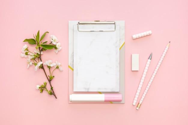 Postura plana de artigos de papelaria de escritório com bloco de notas e flores