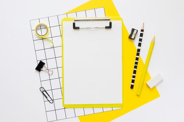 Postura plana de artigos de papelaria de escritório com bloco de notas e lápis