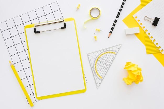 Postura plana de artigos de papelaria de escritório com bloco de notas e papel amassado