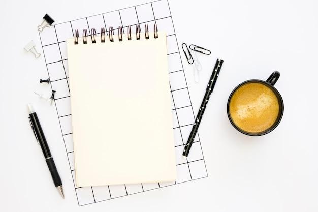 Postura plana de artigos de papelaria de escritório com café e canetas