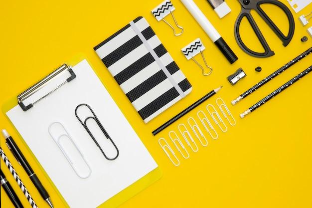 Postura plana de artigos de papelaria de escritório com clipes de papel e blocos de notas