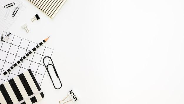 Postura plana de artigos de papelaria de escritório com clipes de papel e lápis