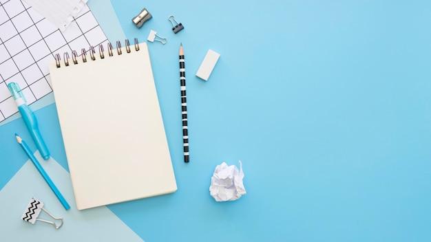 Postura plana de artigos de papelaria de escritório com espaço de notebook e cópia