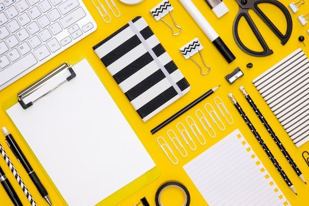 Postura plana de artigos de papelaria de escritório com lápis e teclado