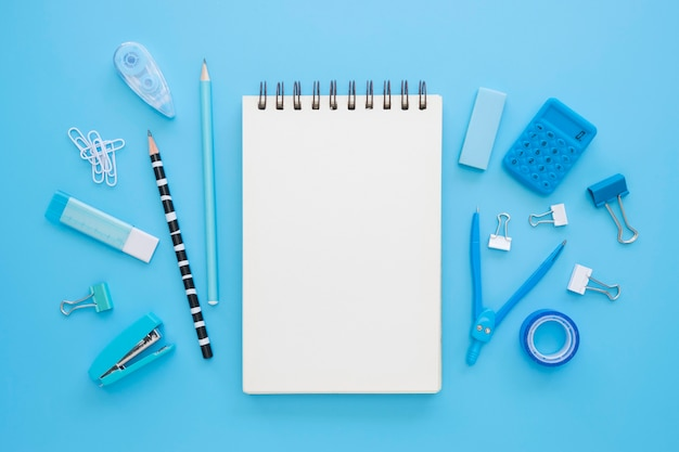 Postura plana de artigos de papelaria de escritório com notebook e bússola