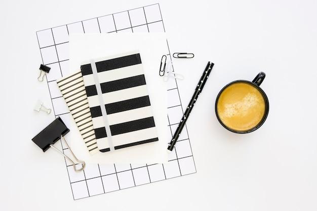 Postura plana de artigos de papelaria de escritório com notebook e café