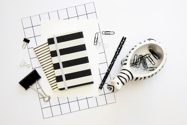 Postura plana de artigos de papelaria de escritório com notebook e decoração