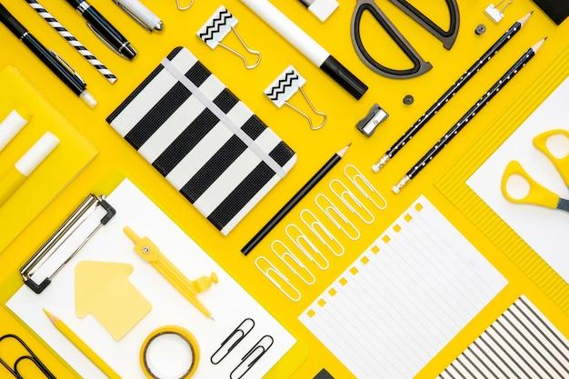 Postura plana de artigos de papelaria de escritório com o bloco de notas e lápis diferentes