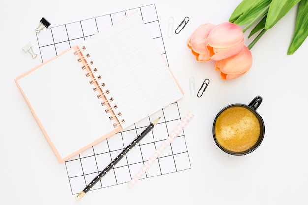 Postura plana de artigos de papelaria de escritório com tulipas e café