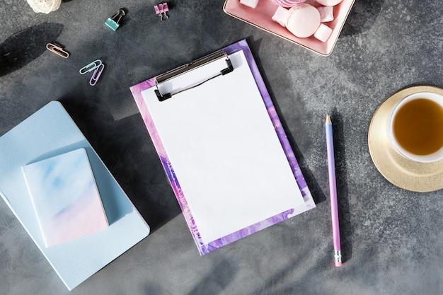 Postura plana de artigos de papelaria de escritório com uma xícara de chá com marshmallow e laptop