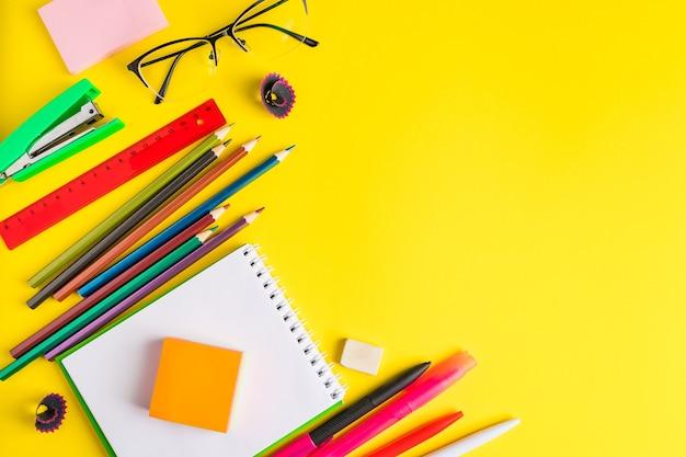 Postura plana de artigos de papelaria em um fundo amarelo. de volta ao conceito de escola. lugar para texto.