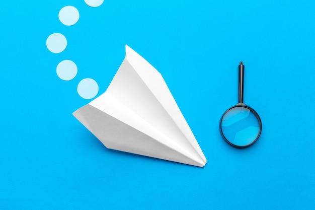 Postura plana de avião de papel branco e papel em branco na cor azul pastel