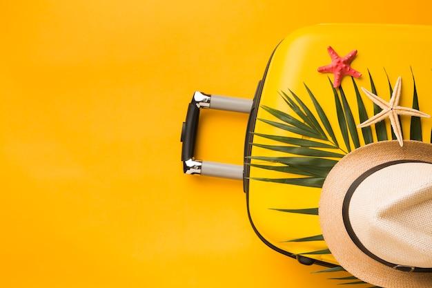Postura plana de bagagem com estrela do mar e chapéu