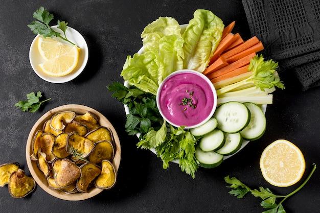 Postura plana de batatas assadas na tigela com legumes
