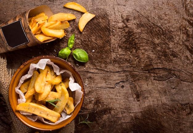 Postura plana de batatas fritas com espaço de cópia e ervas