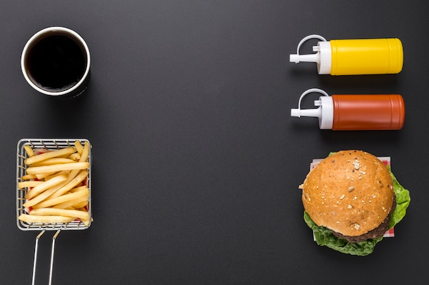 Postura plana de batatas fritas e hambúrguer com ketchup e mostarda
