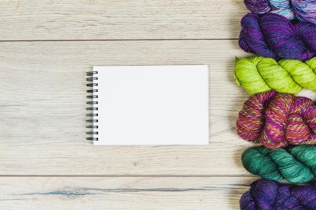 Postura plana de belos novelos em tons de roxos e verdes e caderno em branco para mock-se sobre uma mesa de madeira com espaço de cópia