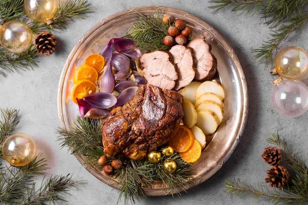 Postura plana de bife de natal no prato com decoração de globos e pinhas