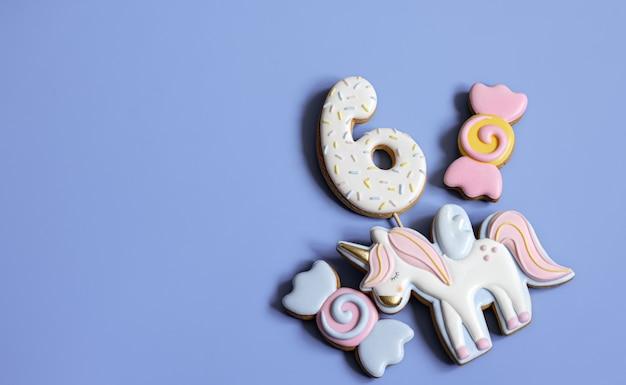 Postura plana de biscoitos de gengibre vitrificados brilhantes na forma de doces em um fundo azul.