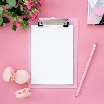 Postura plana de bloco de notas com caneta e macarons