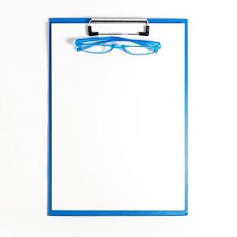 Postura plana de bloco de notas com óculos em cima