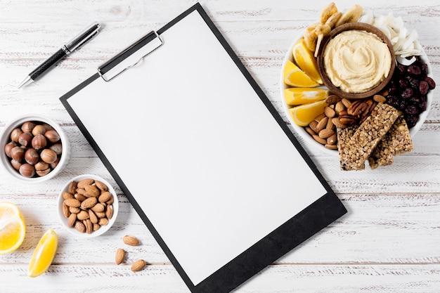 Postura plana de bloco de notas com variedade de nozes e barras de cereais