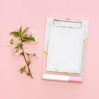 Postura plana de bloco de notas do escritório com flores
