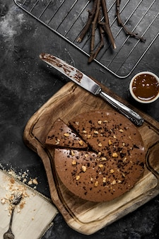 Postura plana de bolo com faca e calda de chocolate