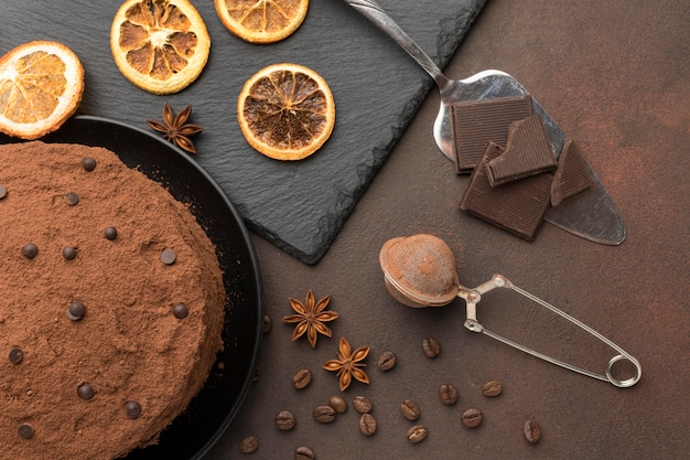 Postura plana de bolo de chocolate com cacau em pó e frutas cítricas secas
