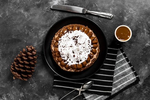Postura plana de bolo no prato com calda de chocolate e pinha