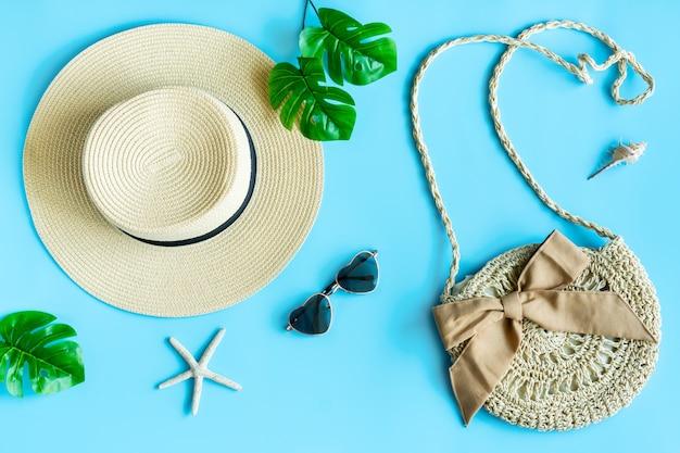 Postura plana de bolsa de verão, óculos de sol, chapéu de praia e folhas de palmeira sobre fundo azul