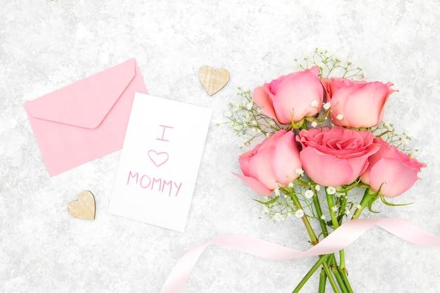 Postura plana de buquê de rosas com envelope