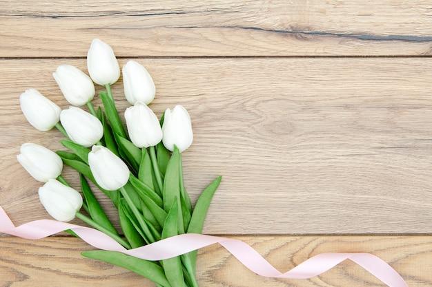 Postura plana de buquê de tulipas na mesa de madeira