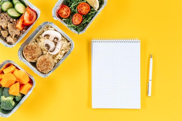 Postura plana de caderno com caneta e refeições em caçarolas