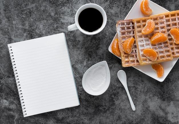 Postura plana de caderno com waffles cobertos com tangerinas