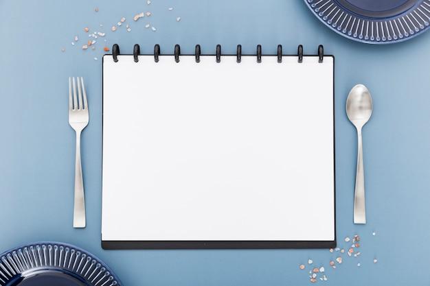 Postura plana de caderno de menu em branco com talheres e pratos