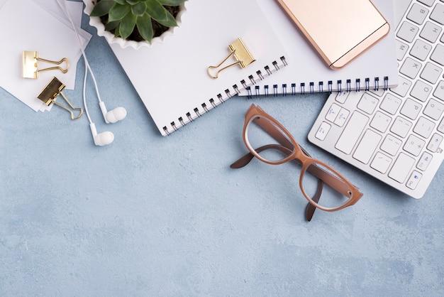 Postura plana de cadernos com teclado e planta suculenta