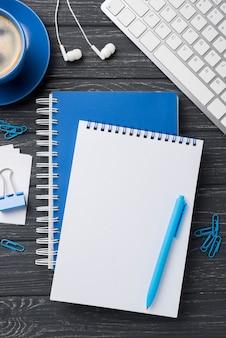 Postura plana de cadernos na mesa de madeira com fones de ouvido e xícara de café