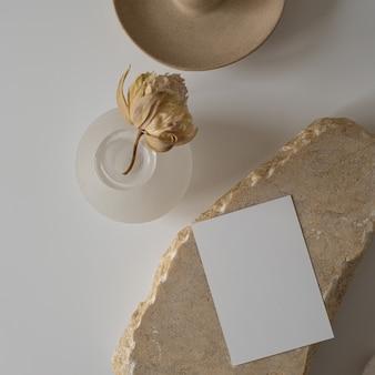 Postura plana de cartão de folha de papel em branco com flor, pedra de mármore