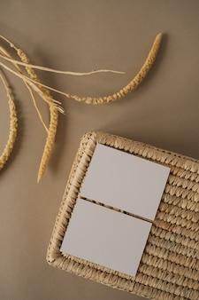 Postura plana de cartões de folha de papel em branco com caixão de vime em bege neutro